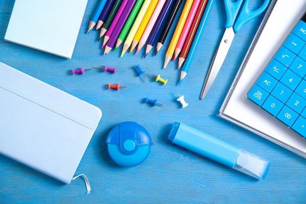Калькулятор, карандаши, записка, ластик, ножницы, маркер, заметки на синей поверхности.