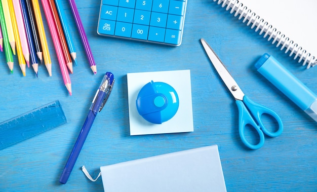 Калькулятор, карандаши, записка, ластик, ножницы, ручка, маркер, заметки на синем фоне.