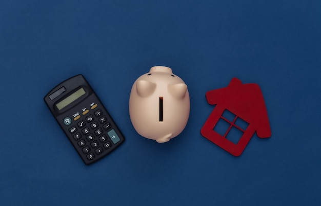 Calculator, piggy bank and house on classic blue background. color 2020. top view
