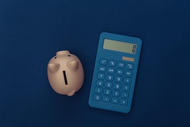 Калькулятор, копилка на классическом синем фоне. цвет 2020. вид сверху.