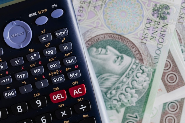 Calculator and polish zloty currency banknotes on a table