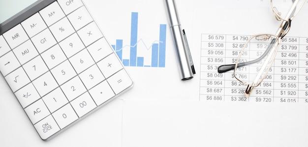 Калькулятор, очки для чтения и карандаши на белом фоне