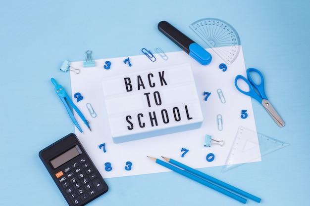 Калькулятор, линейка, маркер, скрепки, компасы, ножницы и надпись обратно в школу