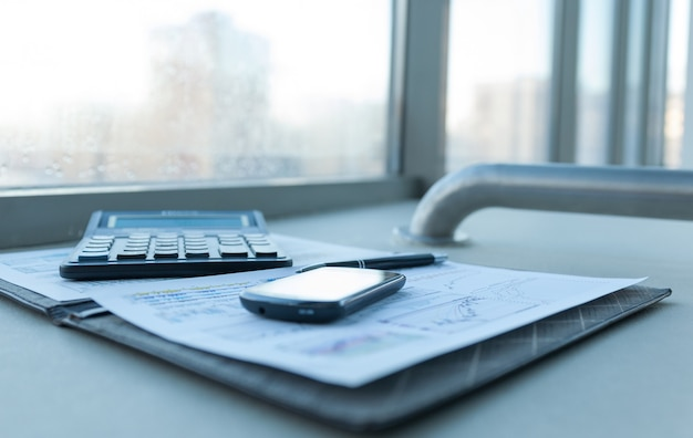 Calculator, smartphone and financial documents on the businessm