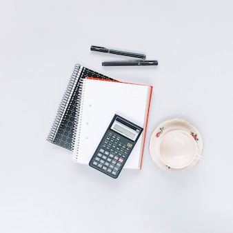 Calculator on spiral notebook with pen and empty ceramic cup on white backdrop