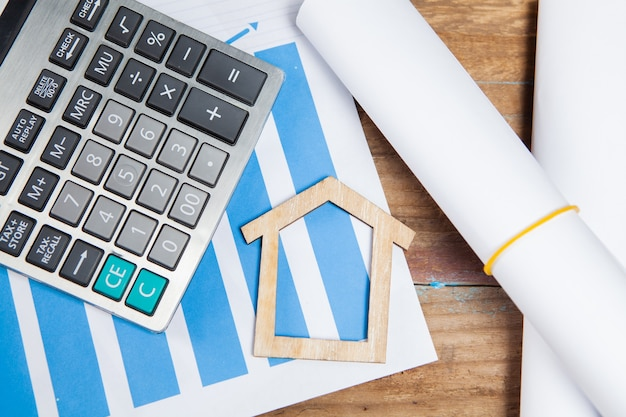 Calculator, statistics and house on a wooden table