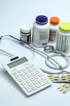 Calculator, stethoscope and medicine bottles on white background