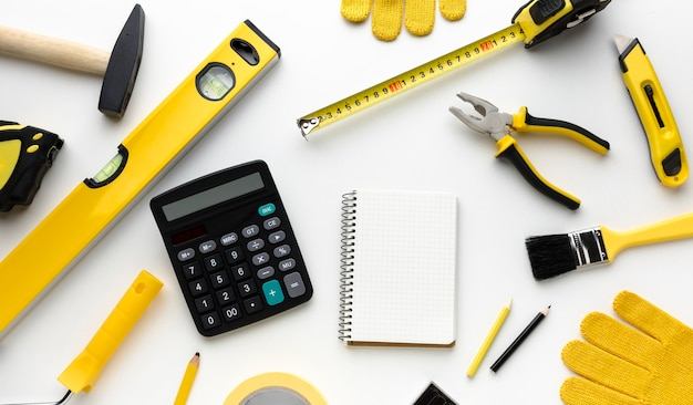 Calculator surrounded by yellow tools and gloves