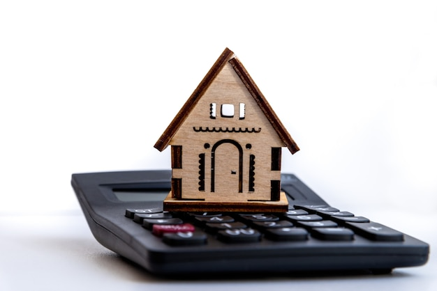 Calculator on table with small house. depicts financial planning for investing or buying a home. property investment planning, home loan, mortgage concept.