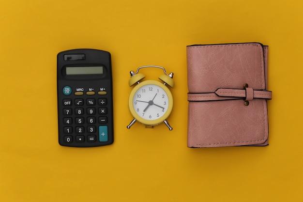 노란색 배경에 계산기, 지갑 및 알람 시계.