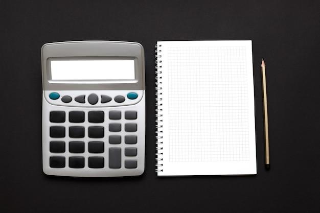 Калькулятор, белый блокнот и карандаш на черной поверхности