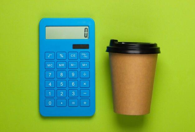 緑の上のコーヒーの段ボールカップと電卓