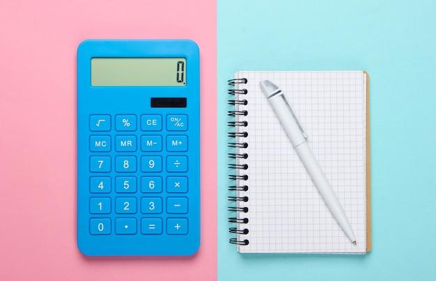 青ピンクのパステル背景にノートブックと電卓。教育プロセス。上面図。フラットレイ