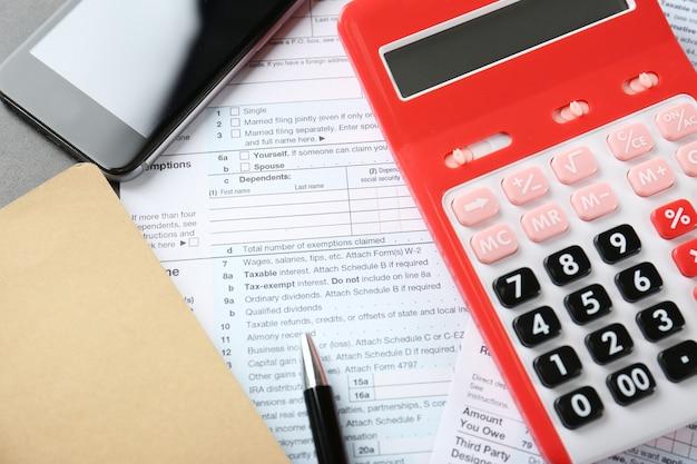 テーブルの上にドキュメントと携帯電話を備えた電卓。税の概念