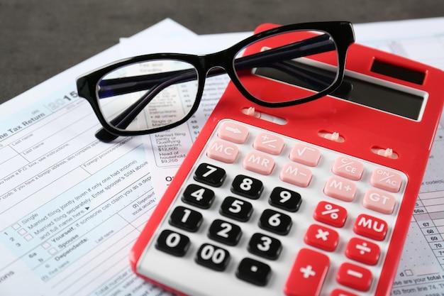 テーブルの上のドキュメントとメガネと電卓。税の概念