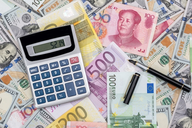 Calculator with euros, dolalr and yuan with pen on desk.