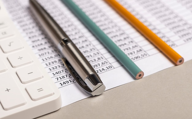 Calculator with financial documents and pens on table close up. workplace of accountant.