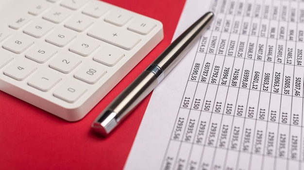 Calculator with financial documents on red table with pen. workplace of accountant.