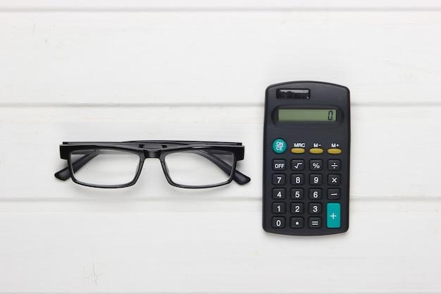 白い木製のテーブルの上の眼鏡と電卓。