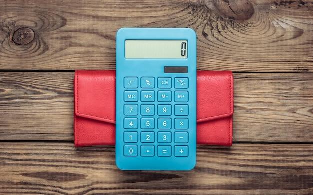 木製のテーブルに革の財布と電卓。ショッピングコストの計算