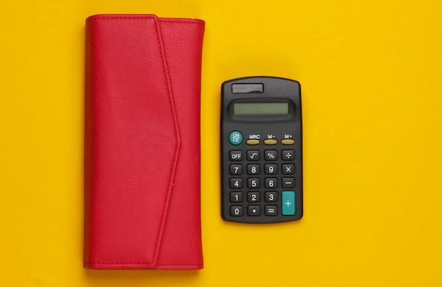 Калькулятор с кожаным кошельком на желтом.