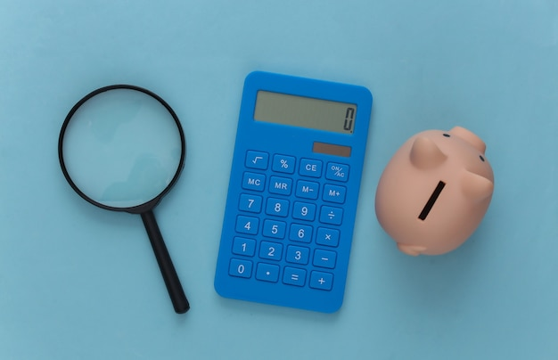 Calculator with magnifier and piggy bank on a blue