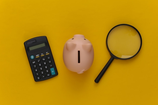 Calculator with magnifier and piggy bank on yellow