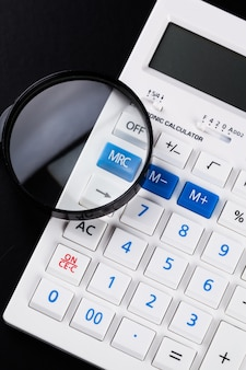 Calculator with a magnifying glass on a black background