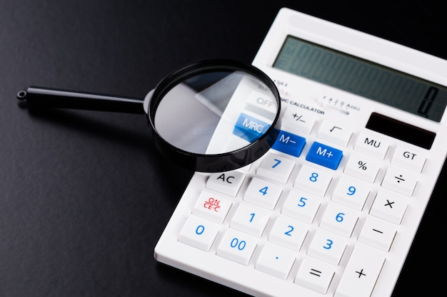 Calculator with a magnifying glass on a black surface