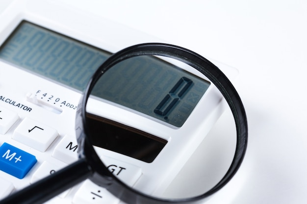 Calculator with a magnifying glass on a white surface
