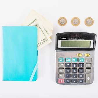 Calculator with money and notebook on table