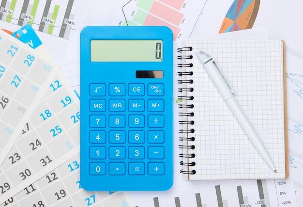 노트북, 그래프 및 차트, 월별 달력이있는 계산기. 경제적 계산, 비용