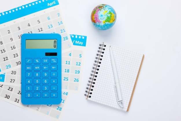 Calculator with notebook, monthly calendar, globe. economic calculation, costing