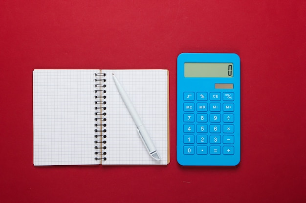 Калькулятор с ноутбуком на красном фоне. образовательный процесс. вид сверху. плоская планировка