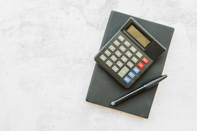 Calculator with notebook on table