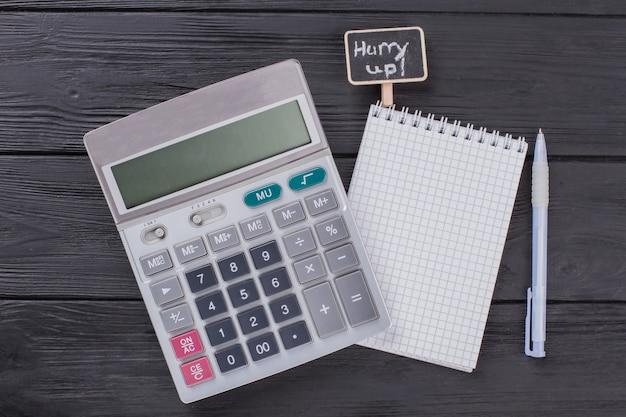 Калькулятор с блокнотом и ручкой. вид сверху крупным планом. темный деревянный фон.