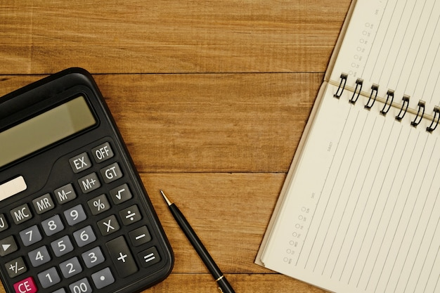 A calculator with a pen and notepad