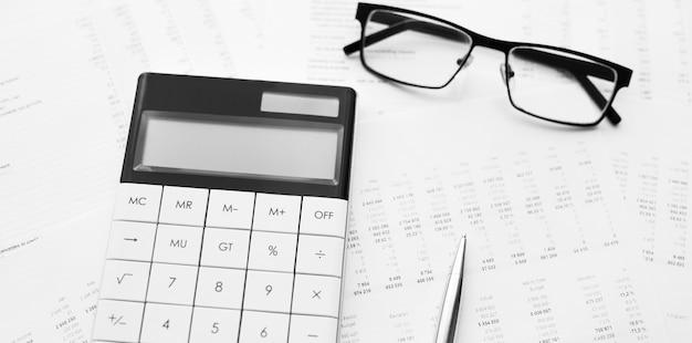 Калькулятор с ручкой на финансовых данных. концепция исследования бизнеса и финансов.