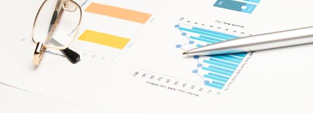금융 데이터에 펜으로 계산기입니다. 비즈니스 및 금융 연구의 개념입니다.