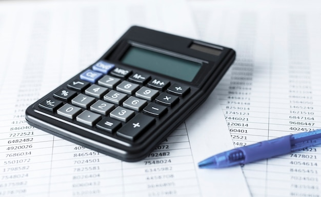 숫자와 흰 종이에 펜으로 계산기입니다. 비즈니스 및 재무 회계 개념.