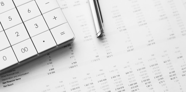 Calculator with pen on stock market analysis. concept of business, finance and audit research.