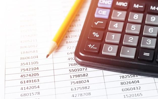 Калькулятор с карандашом на белой бумаге с числами
