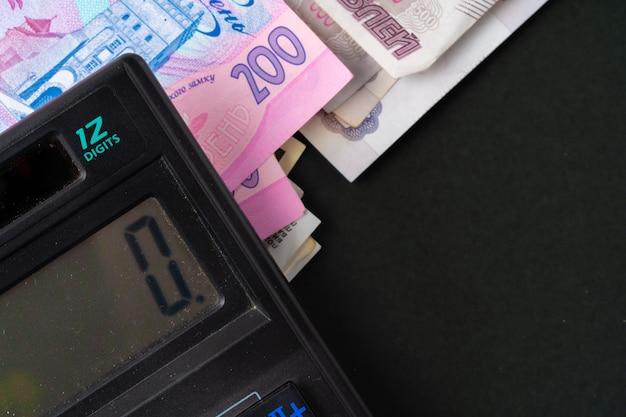 Calculator with pile of money ukrainian hryvnia