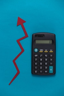 Calculator with red growth arrow on blue. arrow graph going up. the economic growth