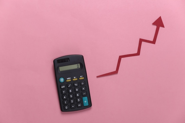 Calculator with red growth arrow on pink. arrow graph going up. the economic growth