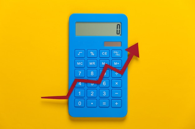 Calculator with red growth arrow on yellow. arrow graph going up. the economic growth