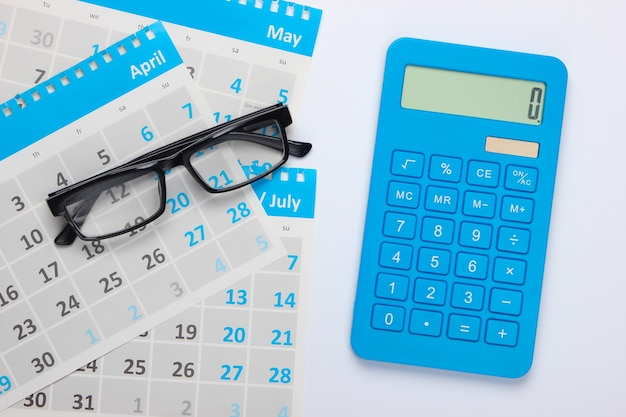 Calculator with sheets of the monthly calendar, glasses on white