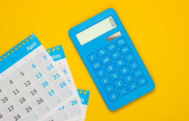 Calculator with the sheets of the monthly calendar on yellow. calculation of rental payments for housing
