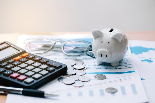 テキストの節税を伴う電卓。電卓、貯金箱、コイン、ビジネスグラフ、木製テーブルのペン。財務会計のためのお金を節約する概念