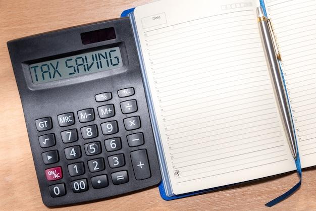 텍스트 세금 절약 계산기. 계산기, 메모장 및 나무 테이블에 펜. 비즈니스, 금융 개념.